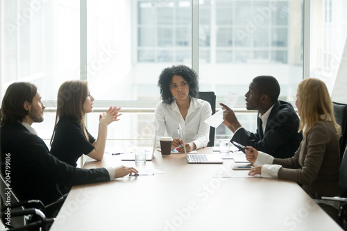 Fototapety, obrazy: Multiracial people having dispute about bad document at group meeting, african businessman disagreeing with contract terms at multi-ethnic negotiations in lawyers office, fraud or legal fight concept