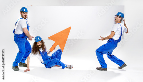 Foto op Plexiglas Artist KB Three handsome craftsmen holding an empty white board