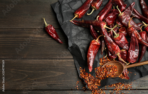 Spoon with chili pepper powder and pods on wooden table