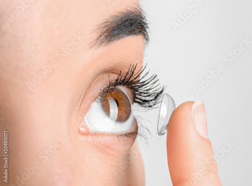 Young woman putting contact lens in her eye, closeup Canvas Print