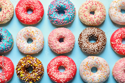 Deurstickers Dessert Delicious glazed doughnuts on color background, top view