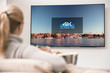 canvas print picture - Big modern TV with 4k resolutions and young woman on foreground watching some video