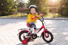 3 Years Old Happy Toddler Boy Riding Red Bike. Little Kid Learns To Ride A Bicycle. Sport, Cycling, Active Playing, And Childhood Concept. First Four-wheeled Bike For Little Child.