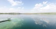 AERIAL: Little pier on a lake. Beautiful rural landscape with flying birds, green dense forest on the coast and endless water surface