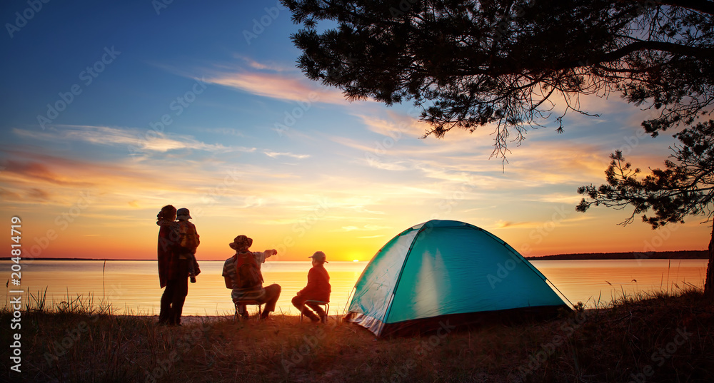 Fototapety, obrazy: Family resting with tent in nature at sunset