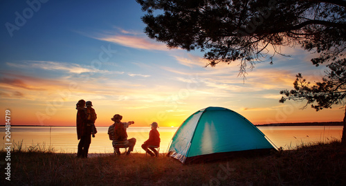 In de dag Kamperen Family resting with tent in nature at sunset