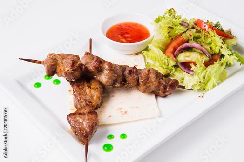 Staande foto Klaar gerecht Shish kebab on bamboo skewers lies on a pita. Near sauce and fresh vegetable salad. White background (close)