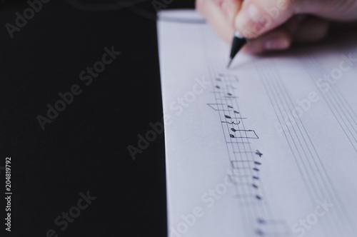 Fotomural Side view of the hand writing the music notes with pencil