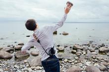 Guy Throwing Rock In Water