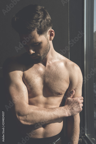 Foto op Plexiglas Akt Masculinity and sensuality. Shirtless young stylish thoughtful man is demonstrating his perfect body while posing near window. Sunshine on his torso