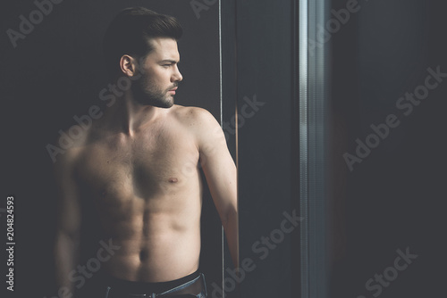 Foto op Plexiglas Akt Feeling hopeless. Profile of young bearded shirtless man with developed muscularity is standing and looking through the window wistfully. Copy space in right side