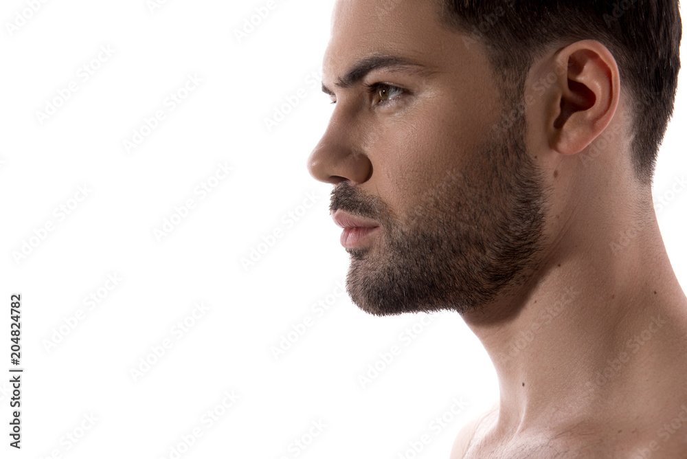 Fototapeta Beauty concept. Close up of profile of young bearded guy is standing and looking forward confidently. Isolated and copy space in the left side