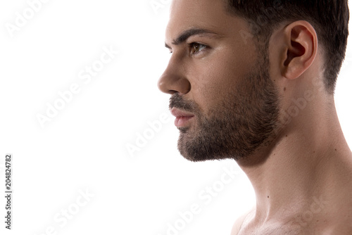 Fototapeta Beauty concept. Close up of profile of young bearded guy is standing and looking forward confidently. Isolated and copy space in the left side obraz