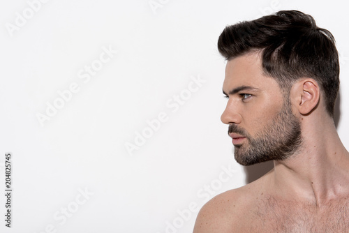Profile of attractive bearded naked guy is standing and looking aside wistfully Wallpaper Mural