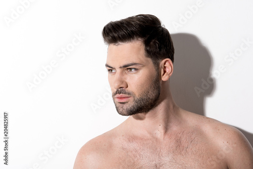 Foto op Plexiglas Akt Side view of gorgeous young bearded naked man is standing and looking aside thoughtfully. Copy space in the left side. Beauty concept