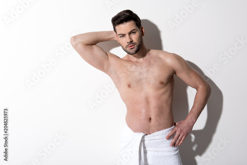 Foto op Plexiglas Akt Portrait of pensive young bearded man is standing with towel on his hips and looking at camera thoughtfully. He is holding hand behind his head and other one on his hip. Copy space in the left side