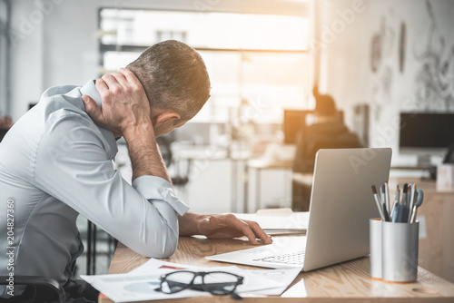 Man holding sore neck while using notebook computer. He sitting at table. Sick worker concept