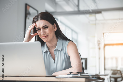 Photo  Portrait of crying girl watching at digital device while having job in office
