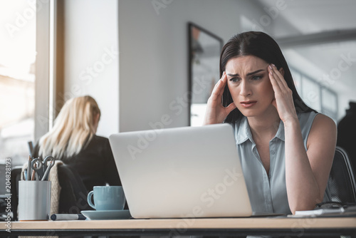 Portrait of disappointed female feeling headache while looking at notebook computer Fototapet