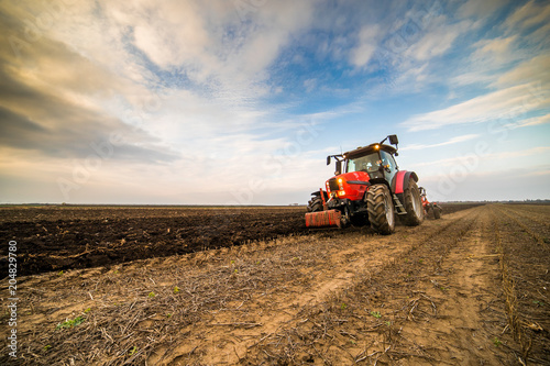 Farmer plowing stubble field