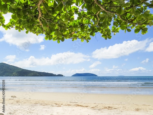 Staande foto Tropical strand View of quiet beach in sunny day with blue sea and island in the background.