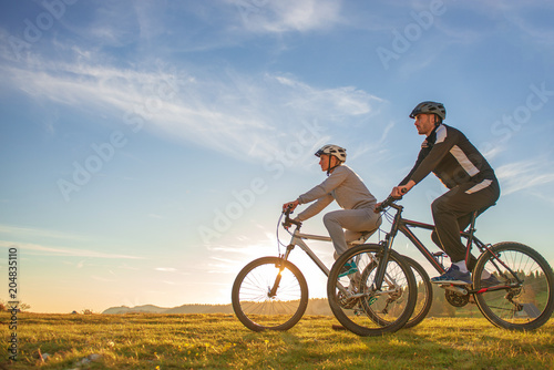 Happy mountainbike couple outdoors have fun together on a summer afternoon sunse Wallpaper Mural