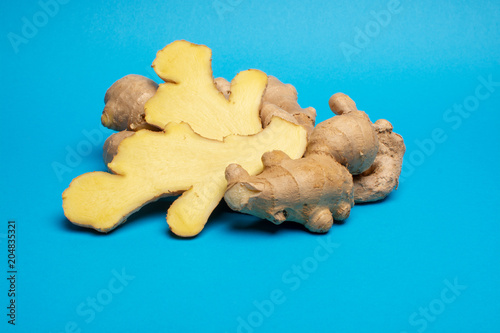 Fototapeta Trendy food concept on blue background with fresh big ginger root close up copy