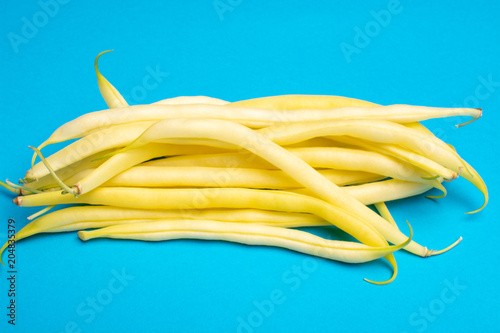 Food concept with fresh legumes, ripe yellow butter beans copy space close up isolated on blue background