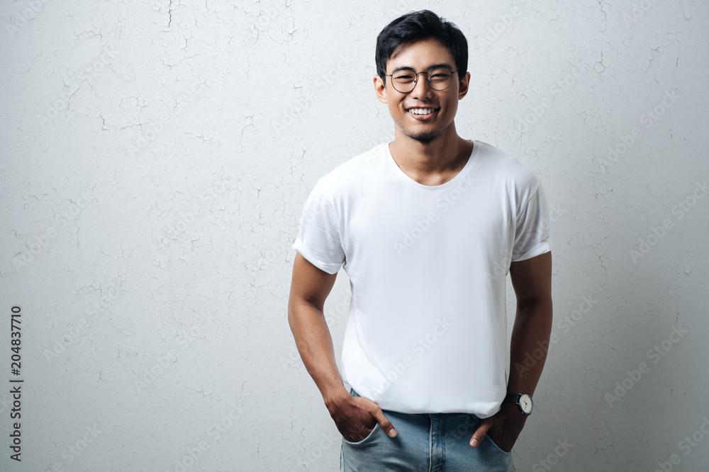 Fototapety, obrazy: Smiling guy in glasses and white blank t-shirt, grunge wall, horizontal studio portrait
