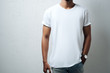 canvas print picture - Guy wearing white blank t-shirt, grunge wall, horizontal studio close-up