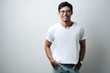 Smiling guy in glasses and white blank t-shirt, grunge wall, horizontal studio portrait