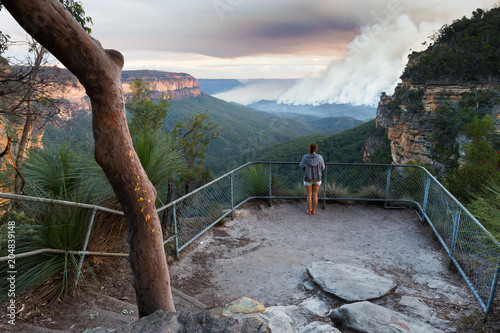 Fototapeta Girl at a bushwalking lookout with a view over a remote bushfire and smoke in the Blue Mountains, New South Wales, Australia