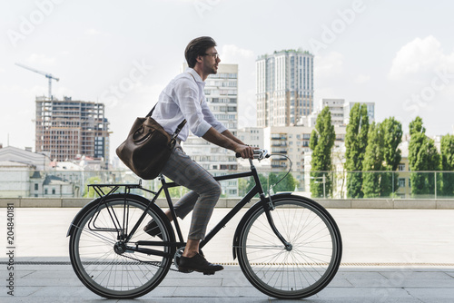 side view of young man in stylish clothes riding vintage bicycle on city street Wallpaper Mural