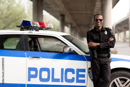 Fotografía  handsome african american police officer with crossed arms leaning back on car a