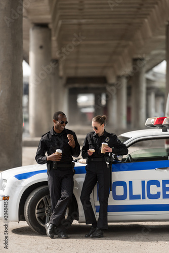 Photo police officers with coffee and doughnuts standing next to car