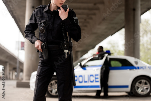 Fotografía  cropped shot of policewoman using walkie-talkie with blurred partner near car on