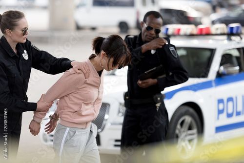 Photo policewoman holding arrested young woman while her partner talking on portable r