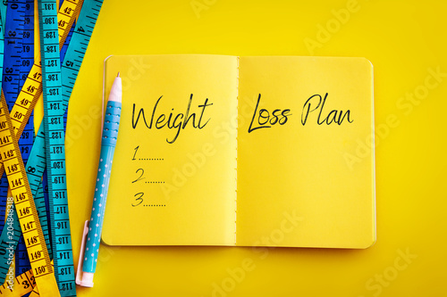 """Weight loss and Diet control concept background. Colorful of Measuring tape on vibrant yellow color background with blue book diary notepad and text as """" Weight Loss Plan """" for a healthy fitness ."""