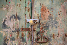 Wooden Peeled Door Background Locked With Rusty Handle And Padlock. Aged Brown, Green Gate, Close Up View With Details.