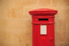 Traditional, British Postbox In Red Color. Mailbox That Receives The Letters. Light Orange Limestone Wall For Background. Copyspace, Close Up View.