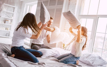The Happy Family Fighting With Pillows On The Bed