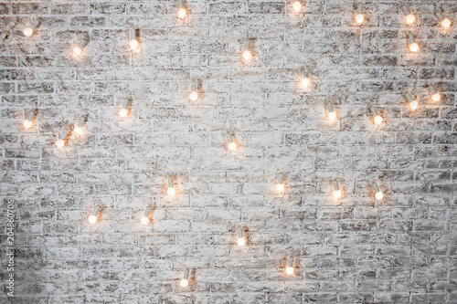 Light Bulbs On White Brick Background. Vintage Edison Light Bulbs Garland  In Loft Interior.