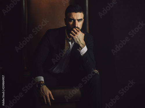 A handsome man with a beard and in a classic suit sits in a leather chair and looks at the camera.