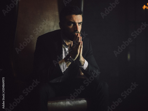 Obraz na płótnie A handsome man with a beard and in a classic suit sits in a leather chair and looks at the camera
