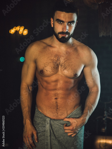 A handsome, muscular man with a beard lies in a bronze bathroom Canvas Print