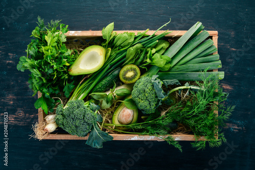 Poster Cuisine Fresh green vegetables and fruits in a wooden basket. Healthy food. Top view. Copy space.