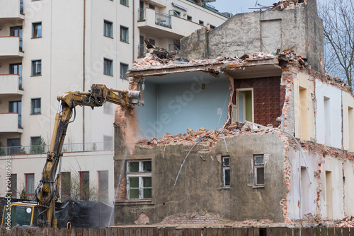 Canvas Old residential building demolition with excavator