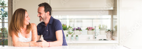Photographie  Middle age couple, woman and man using smartphone at kitchen