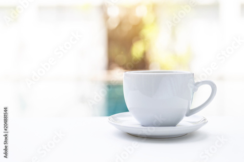 White ceramic coffee cup over blurred swimming pool background, morning outdoor day light