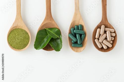 Fotografia  Herbal medicine in spoon on white background